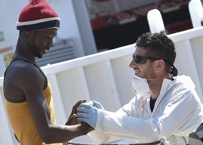 A migrants is helped disembark from Italian Coast Guard ship Diciotti at the Messina harbor in Sicily, Italy, Saturday, Aug. 29, 2015. Migrants by the tens of thousands are braving the perilous journey across the Mediterranean, fleeing war and poverty in the Middle East, Africa and Asia with the hope of reaching Europe and be granted asylum. (ANSA/AP Photo/Carmelo Imbesi)