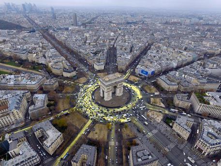 """Un gruppo di attivisti di Greenpeace hanno scalato l'Arco di Trionfo a Parigi, con striscioni che chiedono al governo francese e al presidente Francois Hollande di fare di più per la transizione energetica. Altri militanti hanno invaso la piazza sottostante, dipingendo con """"eco-pittura gialla"""" la grande rotonda e le strade che da lì si diramano per disegnare un grande sole e chiedere così """"un futuro di energie rinnovabili"""", 11 dicembre 2015. ANSA/TWITTER/GREENPEACE +++ ANSA PROVIDES ACCESS TO THIS HANDOUT PHOTO TO BE USED SOLELY TO ILLUSTRATE NEWS REPORTING OR COMMENTARY ON THE FACTS OR EVENTS DEPICTED IN THIS IMAGE; NO ARCHIVING; NO LICENSING +++"""
