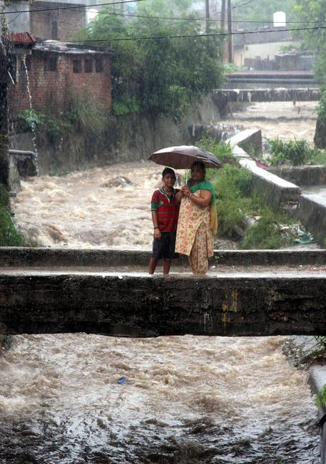 epa05461075 Indian people hold an umbrella to protect themselves from rain during flash floods on the outskirts of Jammu, the winter capital of Kashmir, India, 07 August 2016. According to the news reports, a flood alert was sounded in Jammu as River Tawi was flowing at danger mark of 18 ft, while river Chenab was few centimeters from danger mark of 30.5 feet after incessant rains in the region. EPA/JAIPAL SINGH